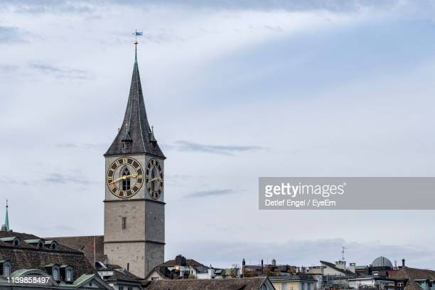 low angle view of clock tower amidst buildings against sky - spire stock pictures, royalty-free photos & images