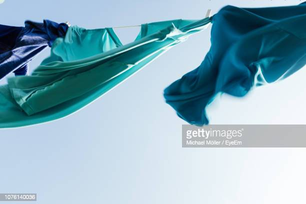 low angle view of clothes drying against sky - 物干し ストックフォトと画像