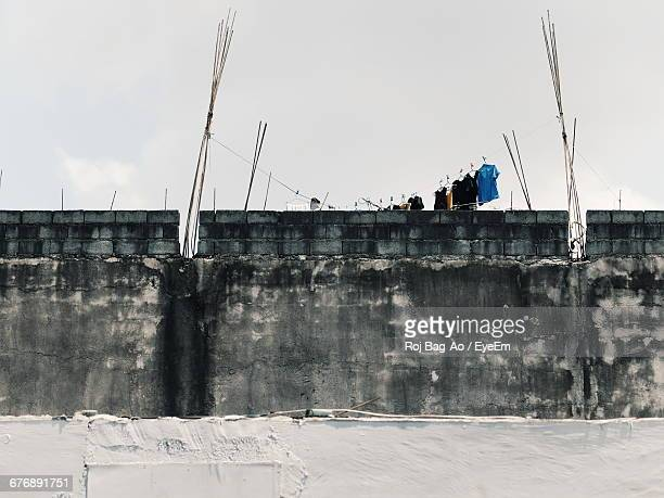 Low Angle View Of Clothes Drying At Construction Site Against Cloudy Sky