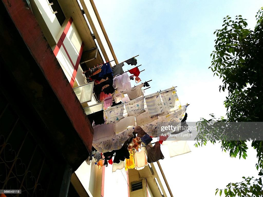 Low Angle View Of Clothes Drying On Rods Against Sky : Stock Photo