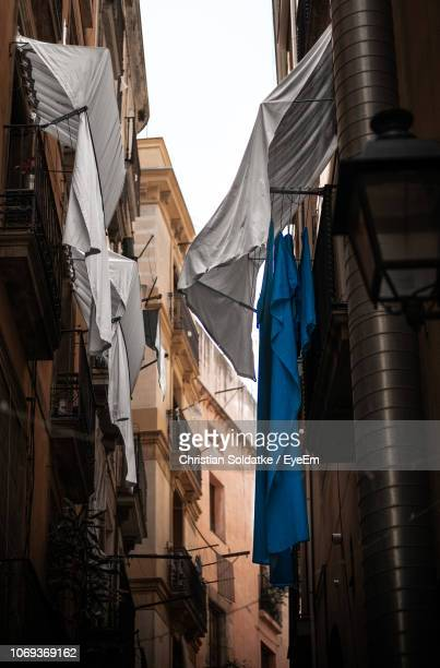Low Angle View Of Clothes Drying Outdoors Of Buildings