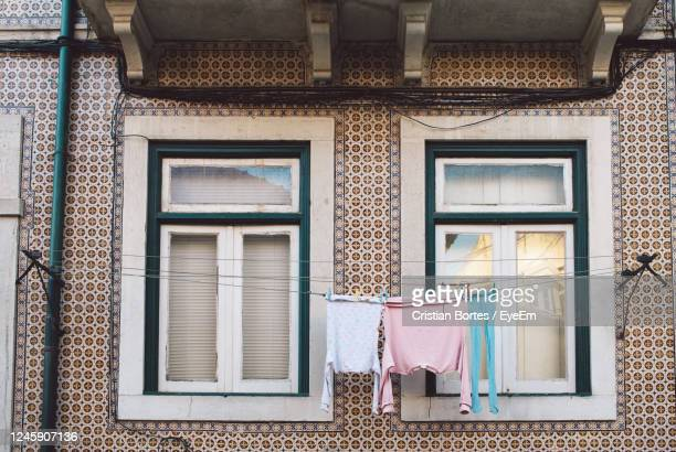 low angle view of clothes drying outside building - bortes stockfoto's en -beelden