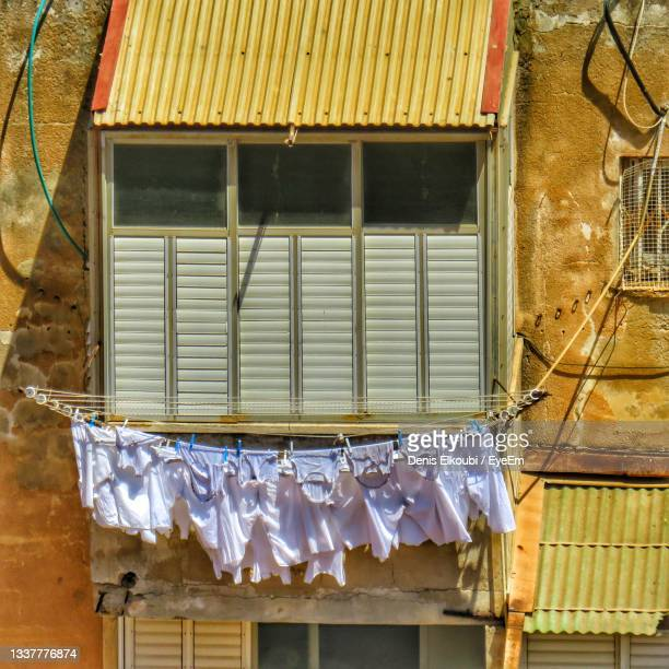 low angle view of clothes drying outside building - netanya stock pictures, royalty-free photos & images