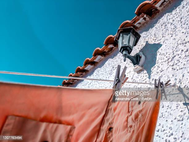 low angle view of clothes hanging against blue sky - alexandra valencia stock-fotos und bilder
