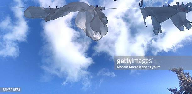 Low Angle View Of Clothes Hanging On Clothesline Against Sky