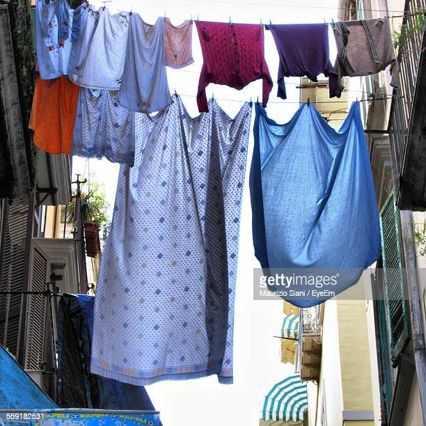 low angle view of clothes lines between buildings - between stock pictures, royalty-free photos & images