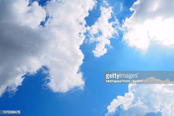 low angle view of clouds in blue sky - metthapaul stock photos and pictures