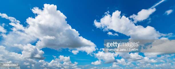 low angle view of clouds in blue sky - clouds stock photos and pictures