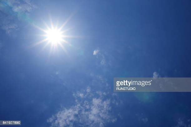 low angle view of clouds in blue sky - suns stock photos and pictures