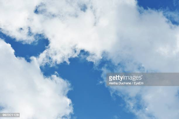 low angle view of clouds in blue sky - duchene stock photos and pictures