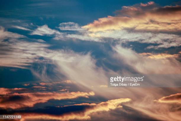 low angle view of clouds in sky during sunset - tolga erbay stock photos and pictures