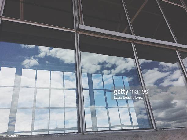 Low Angle View Of Clouds Reflection On Glass Window