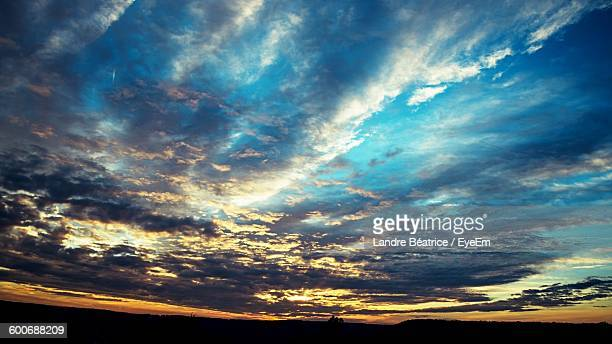 Low Angle View Of Cloudy Sky During Sunset Over Silhouette Landscape