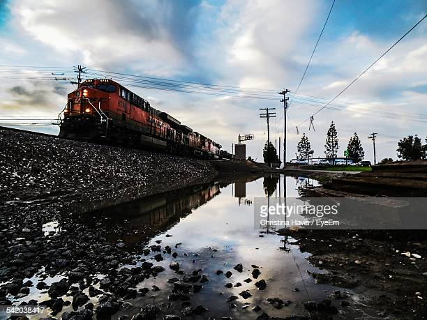 low angle view of cloudy sky over train moving on railway tracks - マーセド郡 ストックフォトと画像