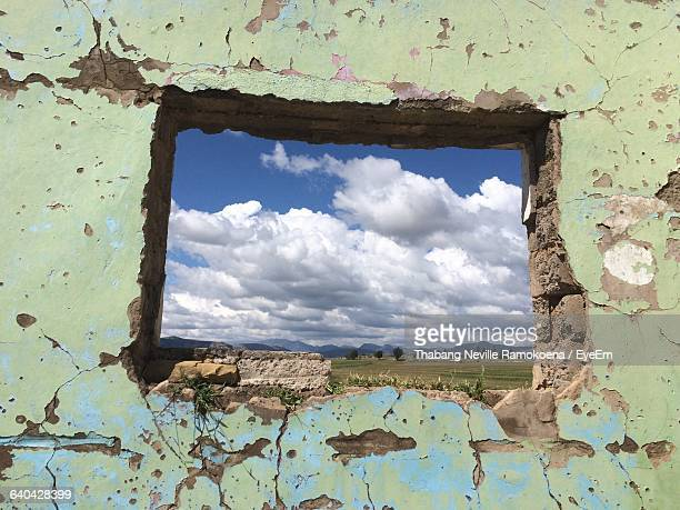 low angle view of cloudy sky seen through window in old building - maseru stock photos and pictures