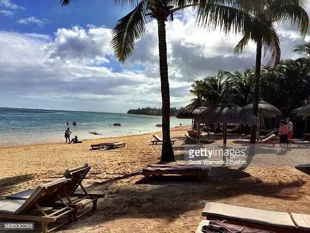 Low Angle View Of Coconut Palm Trees On Beach Against Cloudy Sky