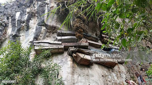 Low Angle View Of Coffins Hanging On Rock Formation