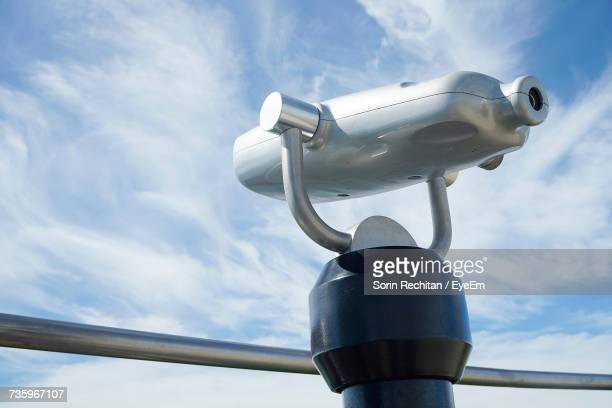 low angle view of coin-operated binoculars against cloudy sky - aussichtspunkt stock-fotos und bilder