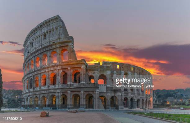 Low Angle View Of Coliseum Against Cloudy Sky During Sunset