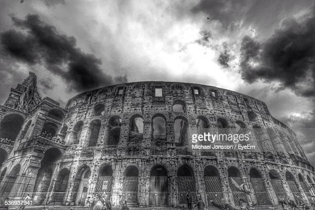 Low Angle View Of Coliseum Against Cloudy Sky