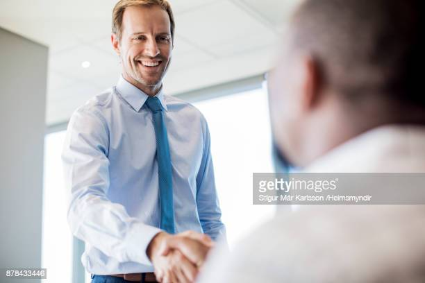 Low angle view of colleagues shaking hands