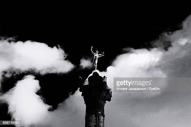 low angle view of colonne de juillet against sky - bastille stock photos and pictures