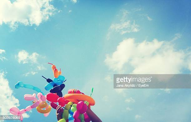 Low angle view of colorful balloons against blue sky
