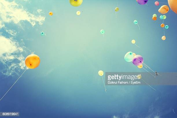 Low Angle View Of Colorful Balloons Flying In Mid-Air Against Sky