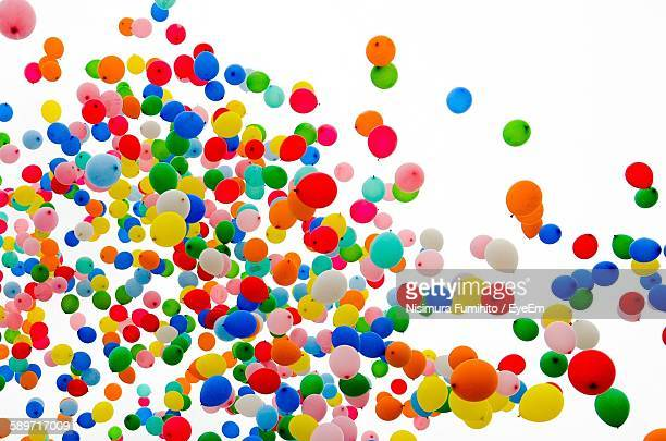 low angle view of colorful balloons in mid-air against clear sky - luftballons himmel stock-fotos und bilder