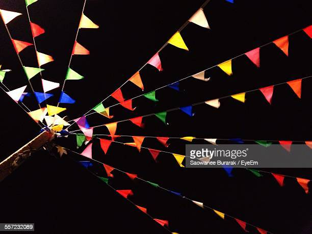 Low Angle View Of Colorful Bunting Against Sky At Night