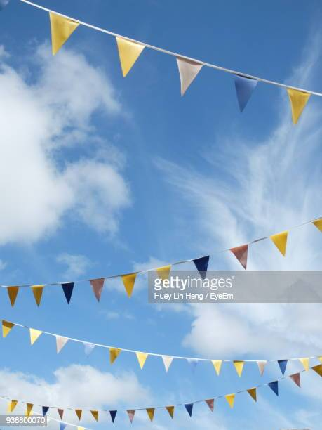 low angle view of colorful bunting flags against sky - bunting stock pictures, royalty-free photos & images