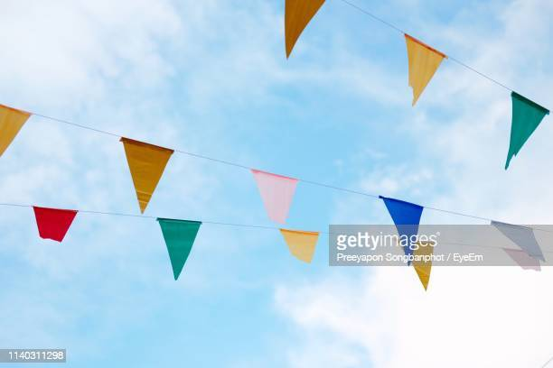 low angle view of colorful buntings against blue sky - bunting stock pictures, royalty-free photos & images