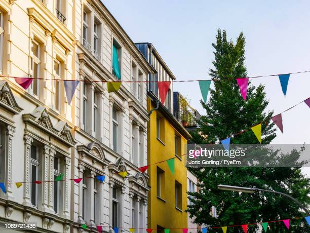 low angle view of colorful buntings hanging against christmas tree in city - banderines fotografías e imágenes de stock