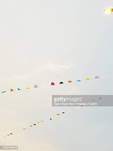 low angle view of colorful buntings hanging against sky - banderines fotografías e imágenes de stock