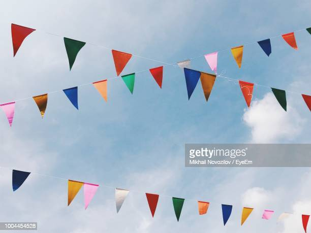 low angle view of colorful buntings hanging against sky - bunting stock pictures, royalty-free photos & images