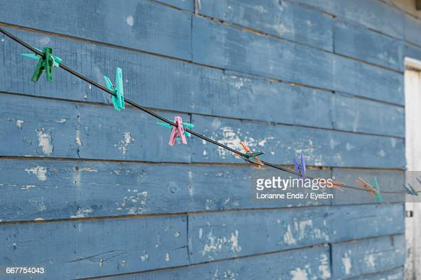Low Angle View Of Colorful Clothespin On String Against Wall
