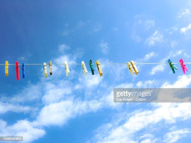 Low Angle View Of Colorful Clothespins Hanging On Clothesline Against Sky During Sunny Day