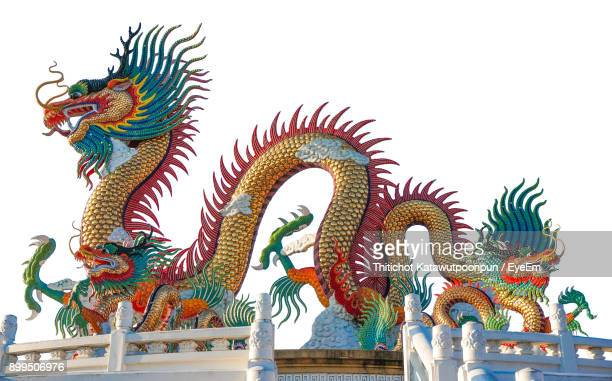 low angle view of colorful dragon statue against clear sky - chinese dragon stock photos and pictures