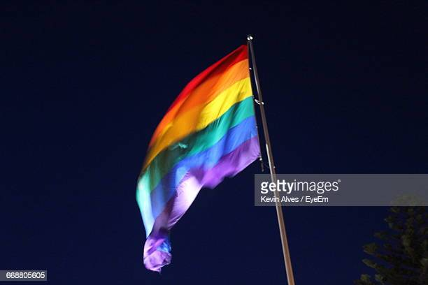 Low Angle View Of Colorful Flag Against Sky At Night