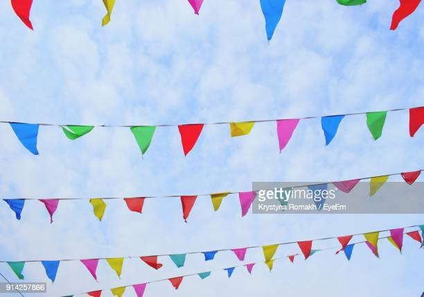 Low Angle View Of Colorful Flags Hanging Against Sky