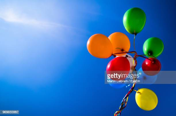 low angle view of colorful helium balloons against sky - helium balloon stock pictures, royalty-free photos & images