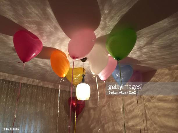 Low Angle View Of Colorful Helium Balloons At Illuminated Home