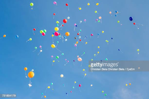 Low Angle View Of Colorful Helium Balloons Flying Against Blue Sky During Sunny Day