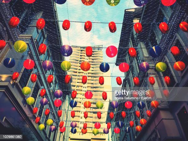 low angle view of colorful lanterns hanging amidst buildings in city - manila philippines stock pictures, royalty-free photos & images
