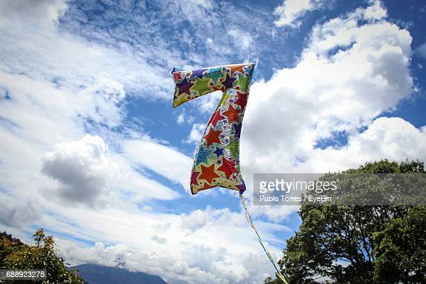 low angle view of colorful number 7 helium balloon against cloudy sky - seven stock pictures, royalty-free photos & images