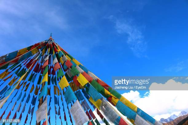 low angle view of colorful prayer flags against blue sky - liu he stock pictures, royalty-free photos & images
