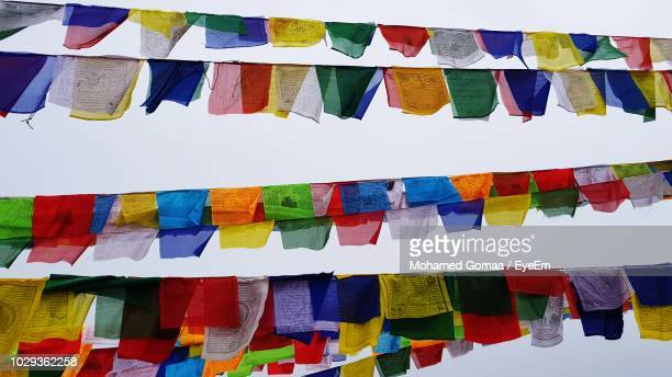 low angle view of colorful prayer flags hanging against sky - nepal fotografías e imágenes de stock