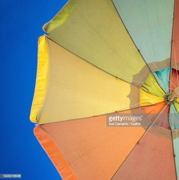 Low Angle View Of Colorful Umbrella Against Clear Blue Sky