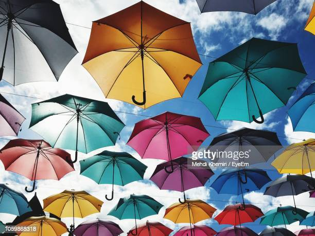 low angle view of colorful umbrellas hanging against sky - umbrella stock pictures, royalty-free photos & images