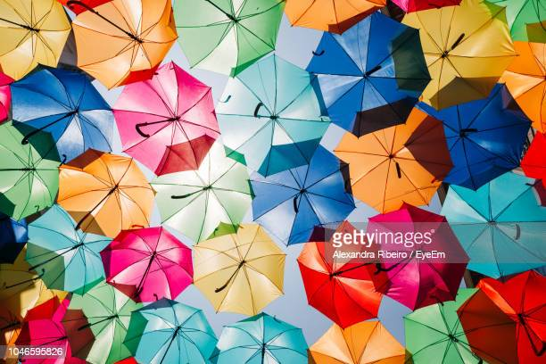 low angle view of colorful umbrellas hanging outdoors - 傘 ストックフォトと画像